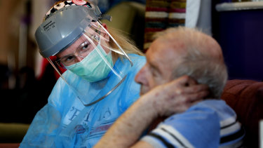 A nurse in personal protective equipment speaks to a resident at a care home in Nottingham.