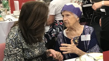 Premier Annastacia Palaszczuk holds hands with 100-year-old family friend Yadja Cartmer at a pre-Christmas function for Queensland's 100 Club.