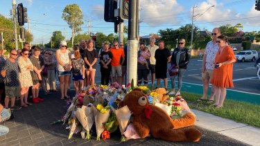 Danielle Leadbetter (far right in the orange dress) looks on as tributes accumulate.