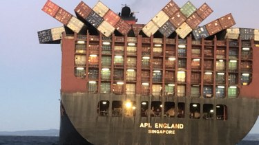 Containers cling precariously to  APL England last Sunday after other cargo fell overboard.