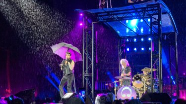 Singing in the rain: Adam Lambert, Brian May and Roger Taylor with various levels of shelter.