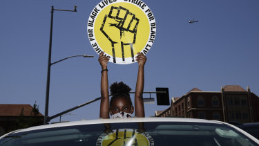Audrey Reed, 8, holds up a sign  during a rally in Los Angeles in July. Thousands of workers across the country walked off the job to protest against systemic racism and economic inequality, which they say has worsened during the coronavirus pandemic.