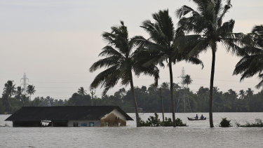 Two men row a boat through a flooded field in Alappuzha, Kerala, on Monday.