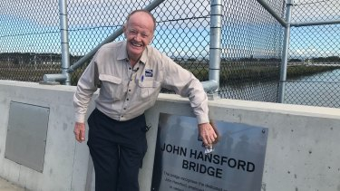 Retiring Brisbane Airport worker John Hansford polishes a sign of his eponymous bridge, commemorating his five decades on the job.
