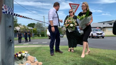 Brisbane lord mayor Adrian Schrinner, his wife Nina, and local councillor Fiona Cunningham place flowers at the scene.