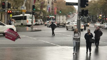 A poster is blown off a traffic light pole and pedestrians shield their faces as strong winds hit Sydney.