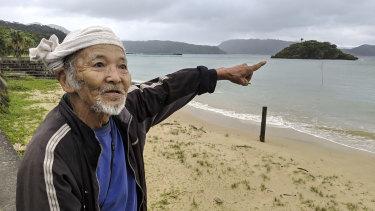Japanese elder Kinsei Ishigaki points to the crash site off the coast of Sonai, Iriomote Jima.