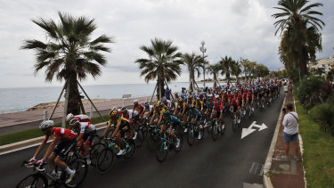 The pack rides along the beach of the Promenade des Anglais during the first stage of the Tour de France cycling race over 156 kilometers (97 miles) with start and finish in Nice, southern France, Saturday, Aug. 29, 2020.