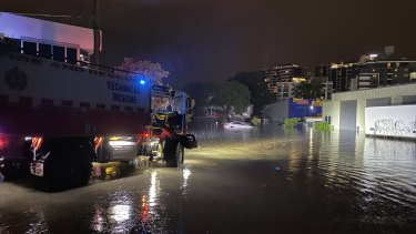 Swift water rescue crews check a floating car in Lotus Street, Woolloongabba last night to ensure nobody is inside.
