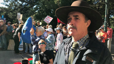 Galilee Basin cattle farmer Bruce Currie protests outside Queensland's Parliament House as scientists evaluate Adani's Carmichael mine groundwater study.