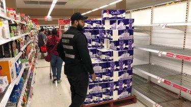 Security guarding toilet rolls as Mt Druitt Coles re-stocks the shelves.