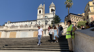 An official looks on as tourists come down the Spanish Steps in Rome.
