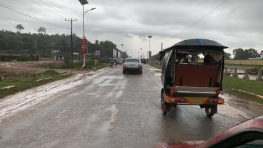 A Rolls-Royce and a tuk-tuk drive towards Sihanoukville Airport.