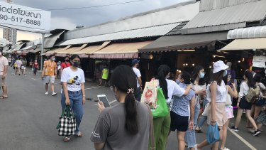 The crowds at Chatuchak Weekend Market have shrunk and shoppers are all wearing face masks.