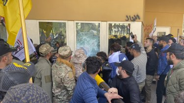 Protesters smash a window inside the US embassy compound, in Baghdad, on December 31.
