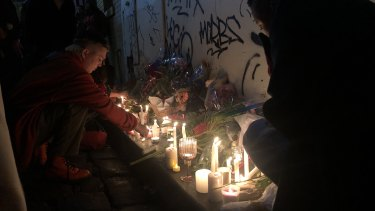 A mourner lights a candle in Celestial Avenue in Chinatown, following the vigil at Federation Square.