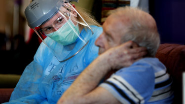 A nurse speaks to a resident at a care home in England.