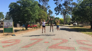 East Loddon P-12 College students Jess Demeo, Stephen Verley and Macey Martin jump for joy on VCE results day in 2019. Dux Stephen Verley's ATAR was spraypainted onto the school's driveway and is still visible to this day.