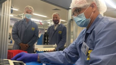 Ellume CEO Sean Parsons and Queensland Deputy Premier Steven Miles overlook a production line of rapid COVID-19 tests.