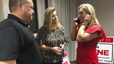 Supporters stand with construction executive Marjorie Taylor Greene, right, as she's on the phone in Rome, Georgia.