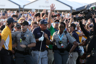 Phil Mickelson is assisted by security as he is followed up the 18th fairway by a gallery of fans after hitting his approach shot during the final round.
