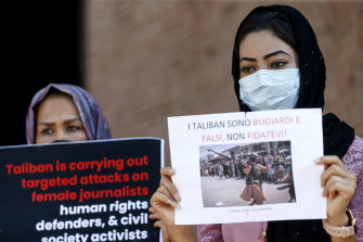 """Members of the Afghan community in Rome hold up posters including one with writing in Italian """"The Taliban are liars and false, don't trust them!"""", during a demonstration."""