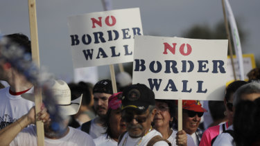 Hundreds of people march along a levee toward the Rio Grande to oppose the wall the US government wants to build on the river separating Texas and Mexico.