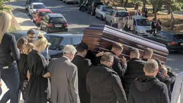 The coffin of John Macris leaves a church in Athens, with widow Viktoria Karyda following.