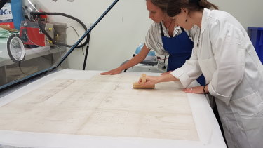 Conservators hard at work in the State Library of Queensland.