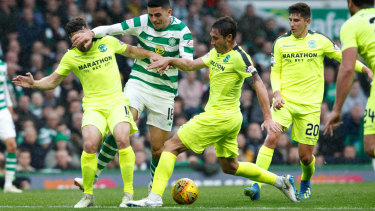 Happy Hibee: Mark Milligan puts in a challenge on Socceroos teammate Tom Rogic while playing for Hibs against Celtic.
