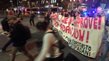 Anti-Adani protesters cross the Victoria Bridge in Brisbane on Friday, June 21, 2019.