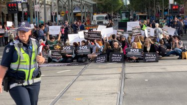 Vegan protesters block one of Melbourne's busiest intersections.