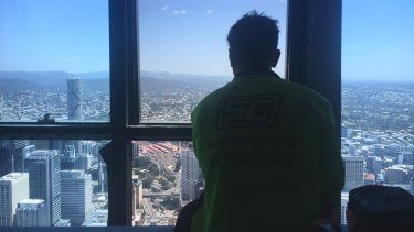"""Tradies enjoy the view from their """"lunch room"""" on the upper floors of Brisbane's Skytower."""