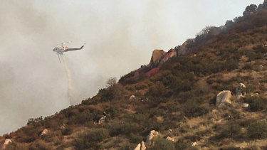 A helicopter makes a water drop on a brush fire in Reche Canyon, California.
