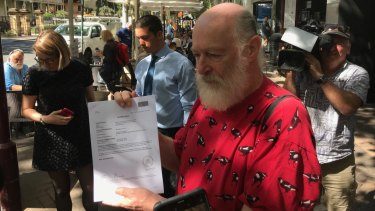 Chris Maltby, treasurer of Local Democracy Matters, holds up orders outside the Land and Environment Court on Tuesday.
