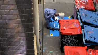 Forensics officers examine a hammer and other items found in Rutledge Lane