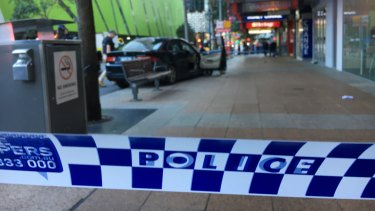 A car is seen on a kerb where pedestrians were hit in the accident in Brisbane's George Street.