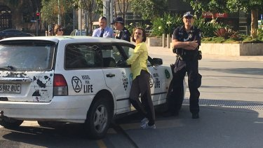 Brisbane protester Eric Herbert locked himself to a car at the base of the Queensland government headquarters.