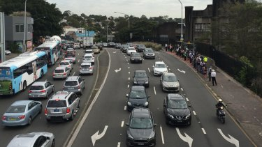Traffic is banked up and passengers wait for buses on Victoria Road due to the ongoing police operation on the Harbour Bridge.