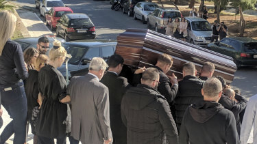 John Macris' coffin leaves the church, with widow Viktoria Karyda following.