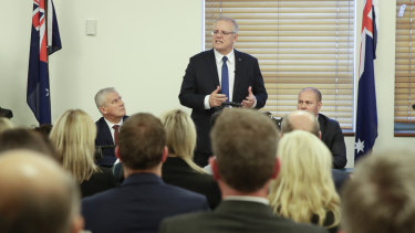 Scott Morrison, flanked by Deputy Prime Minister Michael McCormack and Treasurer Josh Frydenberg, addresses the party room.