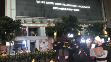 Hong Kong protesters walk past a sign on Nathan Road that reads 'What does your revolution look like?'.