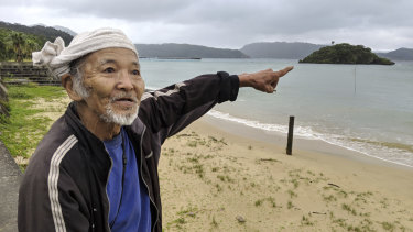 Japanese elder Kinsei Ishigaki points to the crash site off the coast of Sonai, Iriomote Jima.