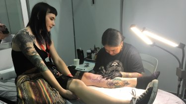 A woman sits for a new tattoo at the Australian Tattoo Expo at the Brisbane Convention Centre on Sunday.
