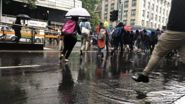 Commuters avoid puddles in the city on Thursday morning.