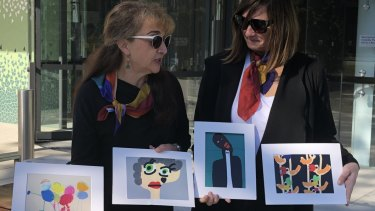 Sarina Marchi and Peta Rostirola, friends of Maria Lutz, displaying Elisa and Martin's artworks outside the Coroners Court in Lidcombe.