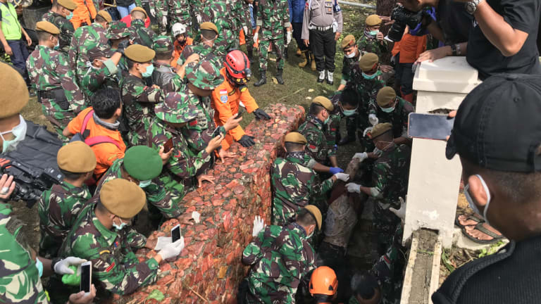 Rescue workers pull a body out of a small cellar, underneath the Tanjung Lesung beach resort's pool.