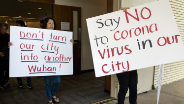 Mary Cahill, left, leaves a news conference where officials discussed the proposal for housing coronavirus patients at the Fairview Development Center in Costa Mesa, California.