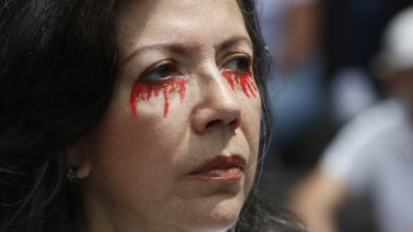 A woman with her eyes painting with red tears participates in an opposition protest against torture and President Nicolas Maduro in Caracas on Venezuela's Independence Day.