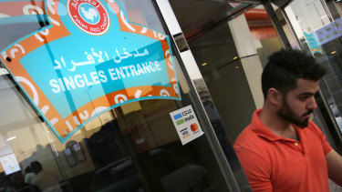 A mean leaves the singles entrance at a restaurant in Jiddah, Saudi Arabia.